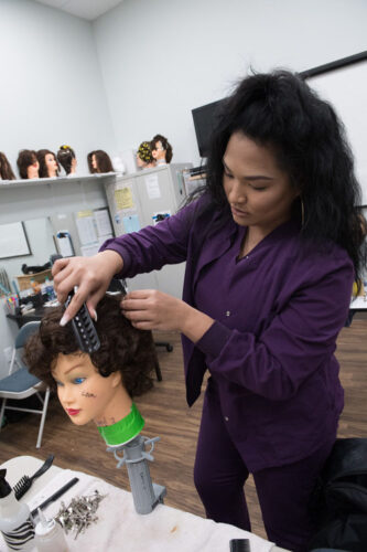 Woman practicing cosmetology on dummy.
